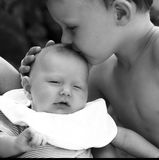 Boy kisses infant Stock Images