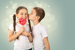 Boy kisses little girl with candy red lollipop in heart shape. Valentine`s day art portrait royalty free stock photos
