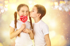 Boy kisses little girl with candy red lollipop in heart shape. Valentine`s day art portrait Royalty Free Stock Photography