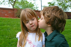 A boy kissing a girl. A four year old boy kissing a girl surrounded by green grass Royalty Free Stock Photos