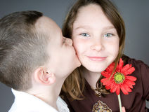 Boy kissing girl with flower. Young boy kissing girl after giving her flower Stock Images