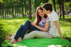 Boy kissing girl out in the park sitting on the grass Stock Image