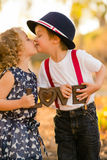 Boy kissing girl. A boy in red suspenders and blue hat kissing curly haired girl in blue dress, holding a love sign Stock Photo