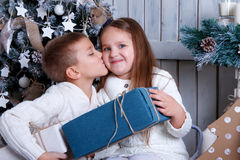 Boy kissing girl under Christmas tree Royalty Free Stock Images