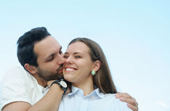 Boy kissing his girl's cheek outdoors on blue sky background Stock Photography