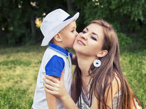 Boy kissing his mother on the cheek outdoors Royalty Free Stock Photos
