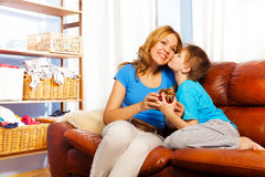 Boy kissing his mother giving gift on the sofa Stock Photography