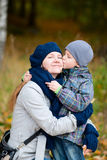Boy kissing his mother outdoor. Autumn portrait Royalty Free Stock Images