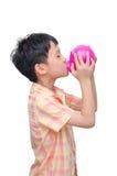Boy kissing his piggy bank Stock Photos