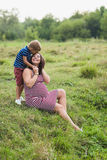 Boy kissing his pregnant mother. Happy mother and her son royalty free stock images