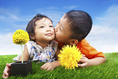 Boy kissing his sister in spring Stock Photo