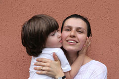 Boy kissing hugging mother Royalty Free Stock Photography
