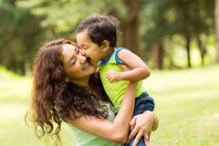 Boy kissing mother. Happy little indian boy kissing mother outdoors Royalty Free Stock Photography