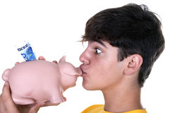 Boy kissing a piggy bank. On white background Royalty Free Stock Photos