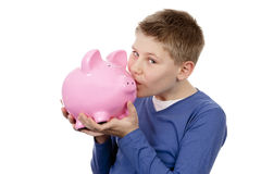 Boy kissing pink piggybank Stock Photo
