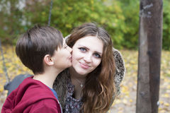Boy kissing teenage girl on her cheek Royalty Free Stock Photography