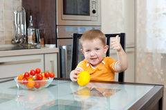 Boy at kitchen with healthy food and showing Stock Photo