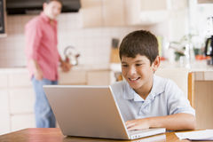 boy kitchen laptop paperwork young