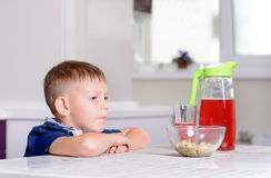 Boy at Kitchen Table with Bowl of Cereal and Juice Royalty Free Stock Images