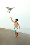 Boy with kite. Young asian boy flying a kite at the beach Royalty Free Stock Photos