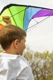 Boy with kite above his head Stock Image
