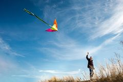 A boy with a kite against the blue sky. Bright sunny day. European appearance boy. Yellow grass stock photos