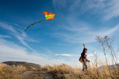 A boy with a kite against the blue sky. Bright sunny day. European appearance boy. Yellow grass stock photo