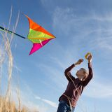 A boy with a kite against the blue sky. Bright sunny day. European appearance boy. Yellow grass royalty free stock image