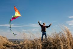 A boy with a kite against the blue sky. Bright sunny day. European appearance boy. Yellow grass royalty free stock photography