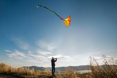 A boy with a kite against the blue sky. Bright sunny day. Flight. In the background is a beautiful landscape, mountains, river royalty free stock image