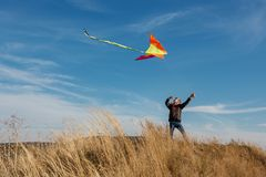 A boy with a kite against the blue sky. Bright sunny day. Flight. A boy of European appearance royalty free stock photos