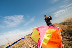 A boy with a kite against the blue sky. Bright sunny day. Strong wind. A boy of European appearance royalty free stock images