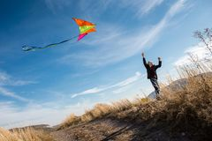 A boy with a kite against the blue sky. Bright sunny day. Strong wind. A boy of European appearance, dressed in jeans and a black stock photography
