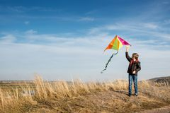 A boy with a kite against the blue sky. Bright sunny day. Strong wind. A boy of European appearance, dressed in jeans and a black royalty free stock image