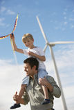 Boy With Kite Sitting On Father's Shoulders. Little boy with kite sitting on father's shoulders at wind farm Royalty Free Stock Image