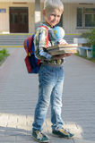 A boy with a knapsack, books and a globe goes to school after a long summer. A boy with a knapsack, books and a globe goes to school after a long summer Royalty Free Stock Image