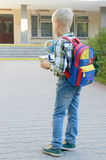 A boy with a knapsack, books and a globe goes to school after a long summer. A boy with a knapsack, books and a globe goes to school after a long summer Royalty Free Stock Photos
