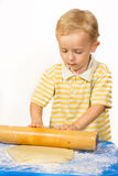 Boy knead the dough by hand for making a cake Royalty Free Stock Image