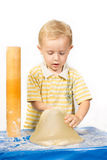 Boy knead the dough with a rolling pin for a cake and tries to pick it up Stock Photo
