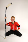 Boy kneeling with hockey stick Stock Photos