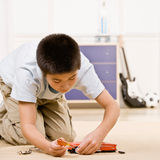 Boy kneeling and putting together parts of a mode Royalty Free Stock Image