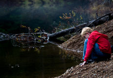 Boy kneels at the side of a mountain lake. Royalty Free Stock Images