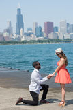 Boy on knees before his mate. A young handsome boy proposing a young and beautiful girl by the riverside. Few high rise buildings is seen in this picture Stock Photography