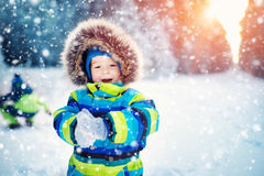 Boy in knitted hat, gloves and scarf outdoors at snowfall Royalty Free Stock Photos