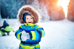 Boy in knitted hat, gloves and scarf outdoors at snowfall Royalty Free Stock Image