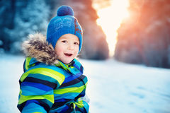 Boy in knitted hat, gloves and scarf outdoors at snowfall Royalty Free Stock Photography