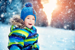 Boy in knitted hat, gloves and scarf outdoors at snowfall Stock Photo