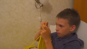 Boy is knitting a scarf with knitting needles. Learning how to knit. Homework. 10 years old boy is knitting a scarf with knitting needles stock footage