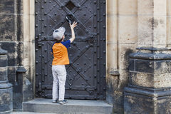 Boy knocking in door knocker on old medieval castle. Royalty Free Stock Image