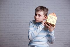 Boy knocking to cardboard toy house and listening. Teen and chil stock photo